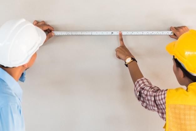 Uomo dell'ingegnere che usando nastro adesivo di misura sulla parete al sito della costruzione di edifici.
