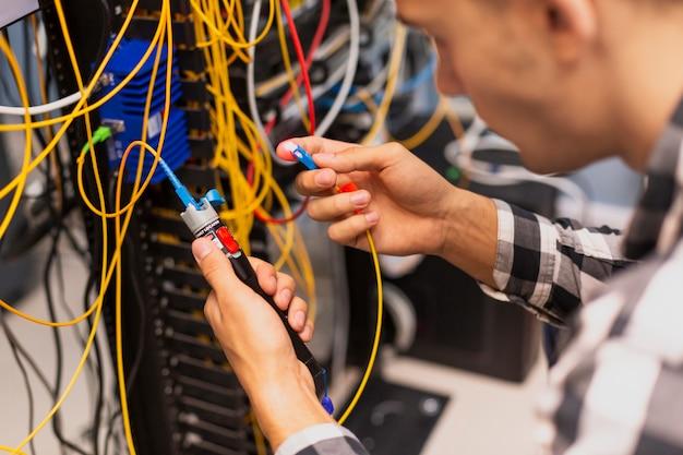 Uomo dell'ingegnere che verifica la fibra ottica