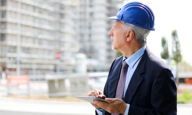 Uomo dell'ingegnere senior in vestito e casco che lavora al pc della compressa