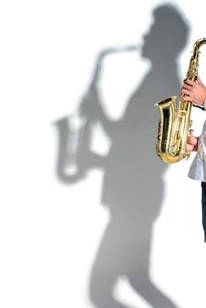 Uomo dell'ombra della siluetta del sassofonista sulla parete bianca.
