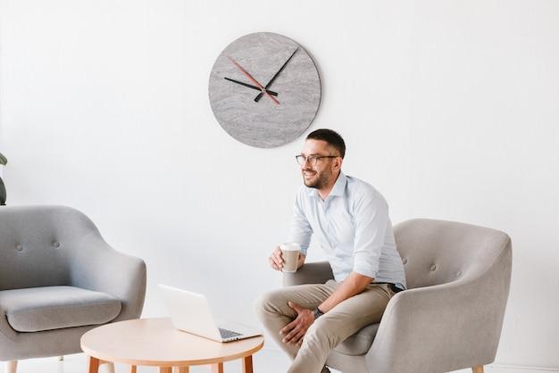 Uomo dell'ufficio diligente 30s in camicia bianca seduto in poltrona e bere caffè da asporto, mentre si lavora al computer portatile nel centro business
