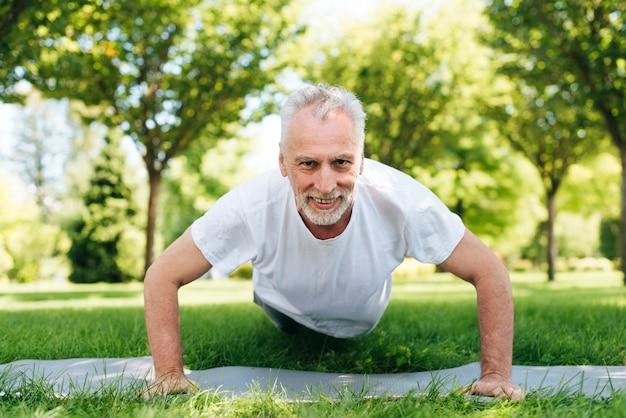 Uomo della foto a figura intera che fa i push-ups all'aperto