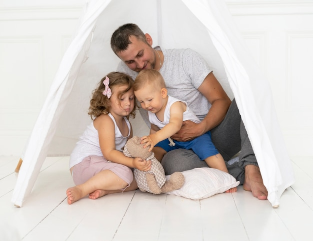 Uomo della foto a figura intera che gioca con i bambini in una tenda