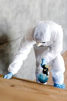 Uomo della foto a figura intera con le scale di disinfezione del vestito