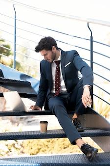 Uomo della foto a figura intera in vestito che lavora alle scale