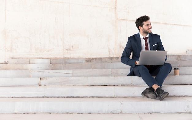 Uomo della foto a figura intera sulle scale che lavorano al computer portatile