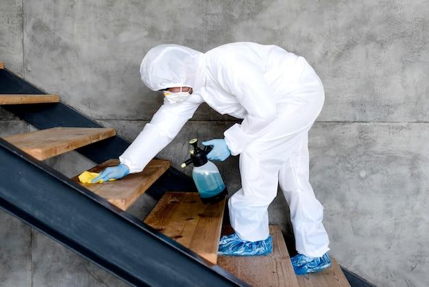 Uomo della foto a figura intera sulle scale con il disinfettante