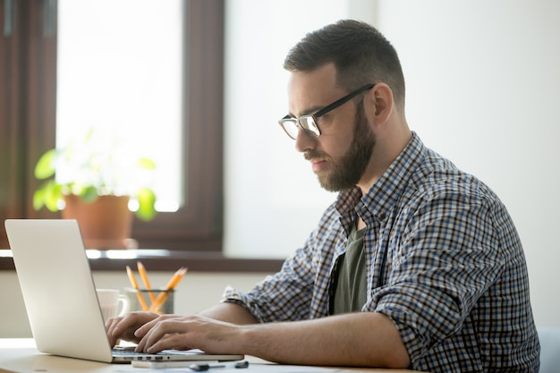 Uomo della generazione del millennio che lavora al computer portatile per risolvere il problema