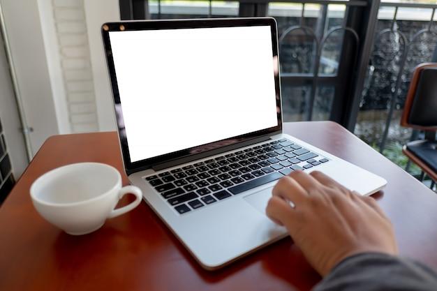 Uomo della mano dell'uomo d'affari che lavora al computer portatile sullo scrittorio di legno