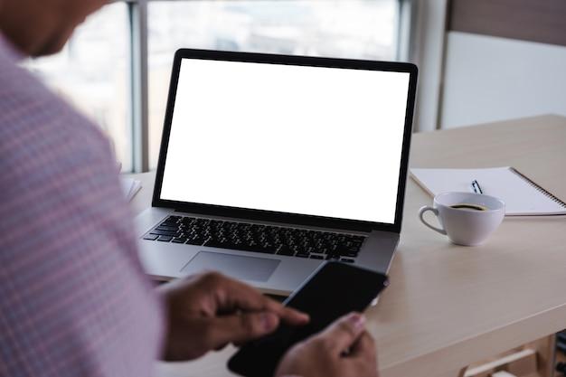 Uomo della mano dell'uomo di affari che lavora al computer portatile dello schermo bianco in bianco del computer portatile