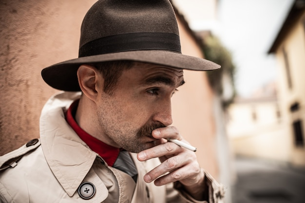 Uomo della spia dell'agente investigativo che cammina in una città