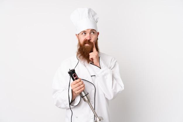 Uomo della testarossa che per mezzo del miscelatore della mano sopra la parete bianca isolata che pensa un'idea