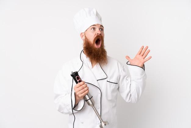 Uomo della testarossa che per mezzo del miscelatore della mano sopra la parete bianca isolata con espressione facciale di sorpresa