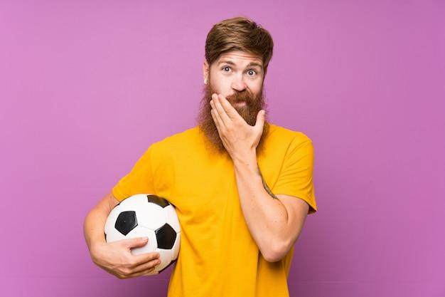 Uomo della testarossa con la barba lunga che tiene un pallone da calcio sopra la parete porpora isolata che pensa un'idea