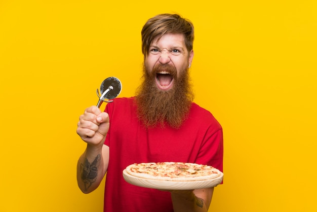 Uomo della testarossa con la barba lunga che tiene una pizza sopra la parete gialla isolata