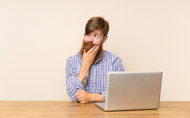 Uomo della testarossa con la barba lunga in una tavola con un computer portatile che pensa un'idea