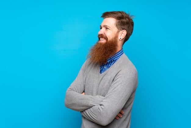 Uomo della testarossa con la barba lunga sopra blu felice isolato e sorridere
