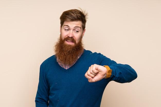 Uomo della testarossa con la barba lunga sopra fondo isolato che guarda l'orologio
