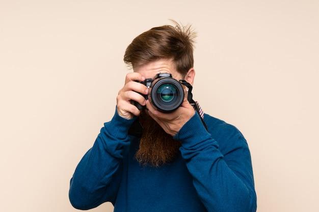 Uomo della testarossa con la barba lunga sopra fondo isolato con una macchina fotografica professionale
