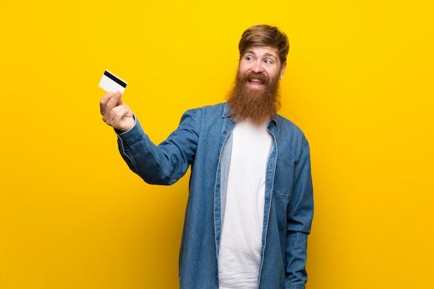 Uomo della testarossa con la barba lunga sopra la parete gialla isolata che tiene una carta di credito