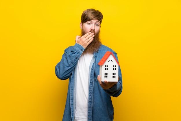 Uomo della testarossa con la barba lunga sopra la parete gialla isolata che tiene una casetta