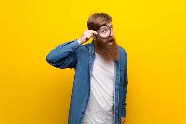 Uomo della testarossa con la barba lunga sopra la parete gialla isolata che tiene una lente d'ingrandimento