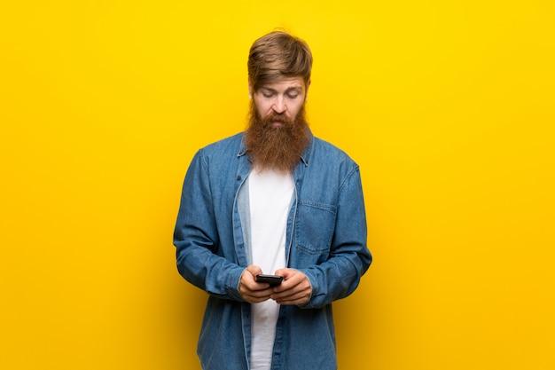 Uomo della testarossa con la barba lunga sopra la parete gialla isolata per mezzo del telefono cellulare