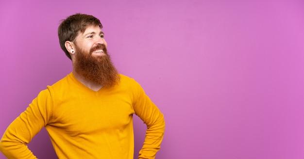 Uomo della testarossa con la barba lunga sopra la posa porpora isolata con le armi all'anca e sorridere