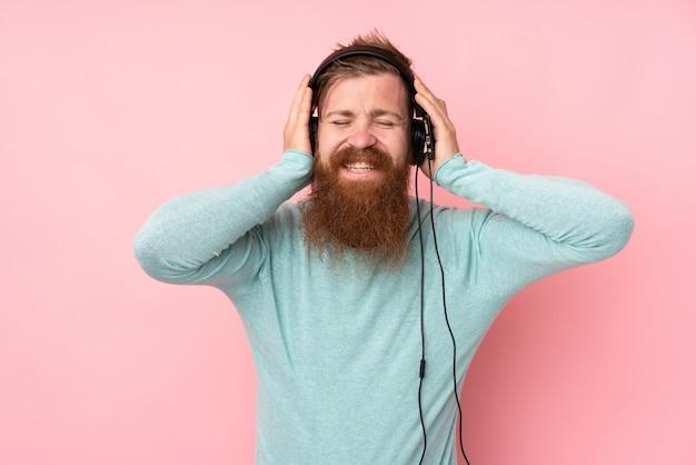 Uomo della testarossa con la barba lunga sopra musica d'ascolto isolata della parete rosa