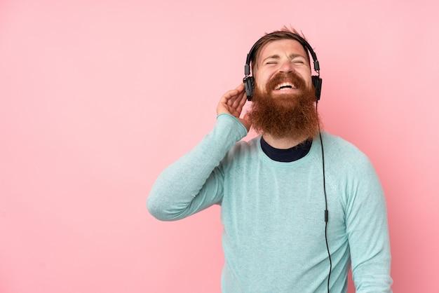Uomo della testarossa con la barba lunga sopra musica e il canto d'ascolto della parete rosa isolata