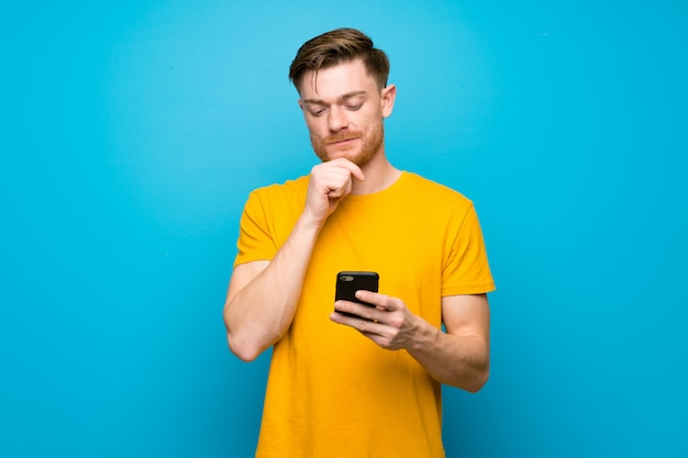 Uomo della testarossa sopra la parete blu che pensa e che invia un messaggio
