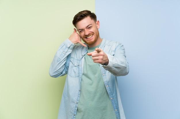 Uomo della testarossa sopra la parete variopinta che fa gesto del telefono e che indica parte anteriore