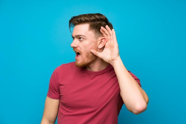 Uomo della testarossa sulla parete blu isolata che ascolta qualcosa