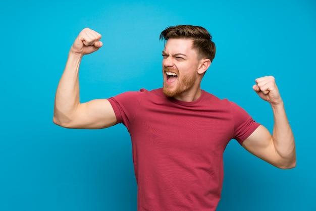 Uomo della testarossa sulla parete blu isolata che celebra una vittoria