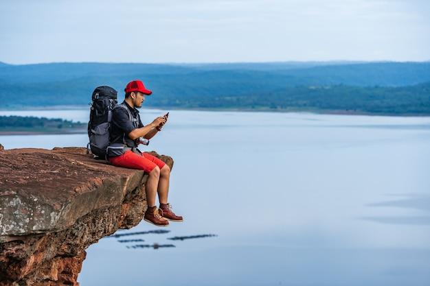 Uomo della viandante che si siede e che per mezzo dello smartphone sul bordo della scogliera, in cima alla montagna della roccia