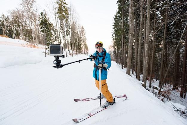 Uomo dello sciatore che prende selfie con il bastone sopra la foresta sulla località di soggiorno di inverno