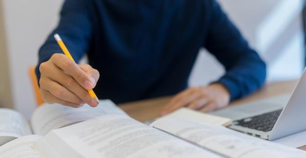 Uomo dello studente che utilizza matita per la lezione sul libro di testo in biblioteca