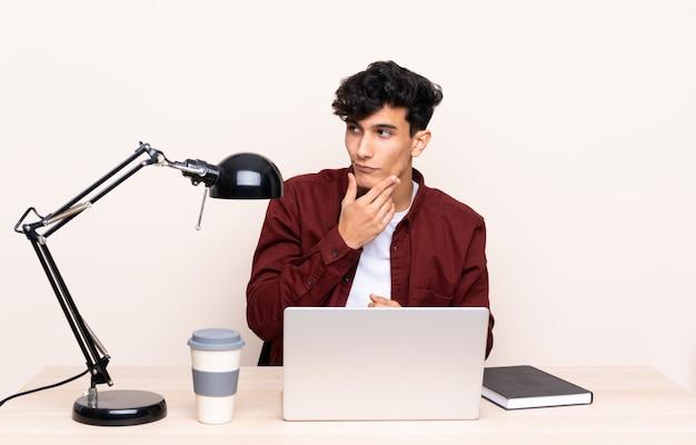 Uomo dello studente in un posto di lavoro con un computer portatile
