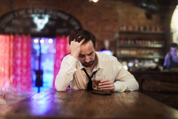 Uomo depresso che beve nel bar