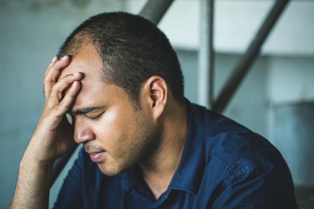 Uomo depresso che si siede con la testa in mano