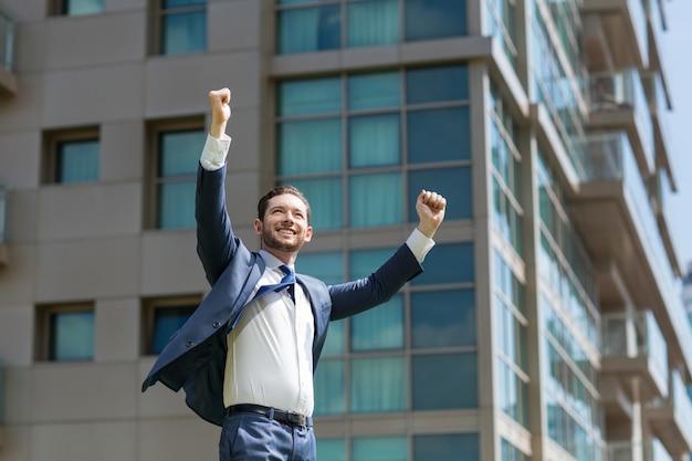Uomo di affari allegro celebrare il successo all'aperto