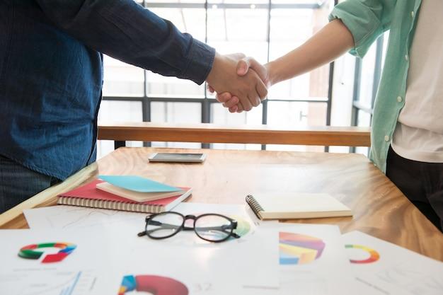 Uomo di affari che agita mano dopo l'analisi del mercato che divide con il cooperatore, concetto del lavoro di gruppo, affare completo