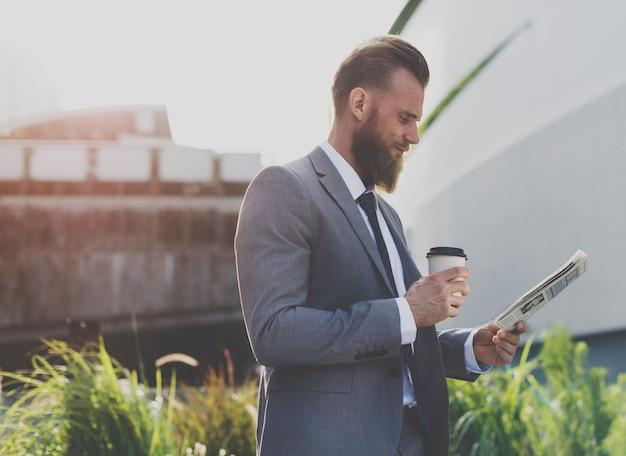 Uomo di affari che beve una tazza di caffè che legge un giornale