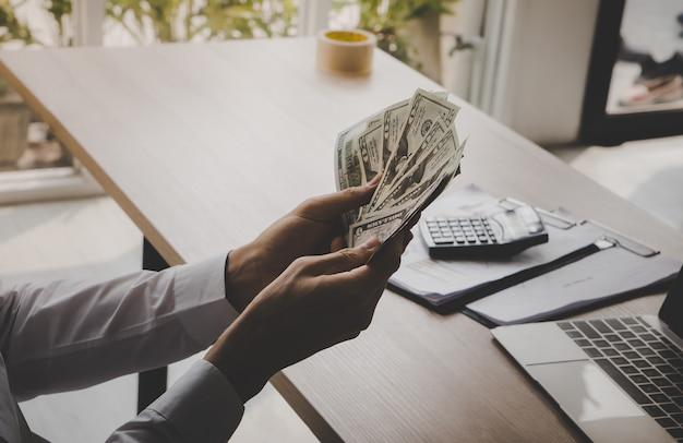 Uomo di affari che conta i soldi della banconota in dollari in ufficio