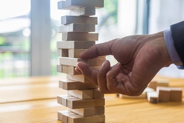 Uomo di affari che gioca con il blocco di legno
