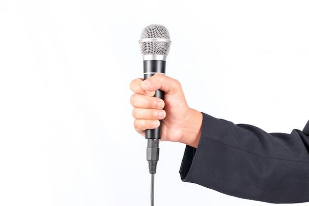 Uomo di affari che giudica un microfono isolato su priorità bassa bianca