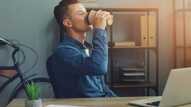 Uomo di affari che lavora all'ufficio con il computer portatile e che beve caffè
