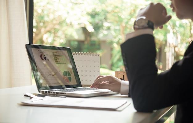 Uomo di affari che lavora all'ufficio con il computer portatile e documenti sul suo scrittorio, concetto dell'avvocato del consulente