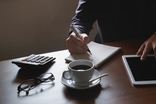 Uomo di affari che lavora alla compressa digitale sulla tavola di legno