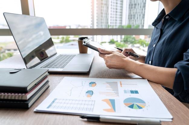 Uomo di affari che lavora con i dati del grafico in computer portatile e documenti sul suo scrittorio all'ufficio.